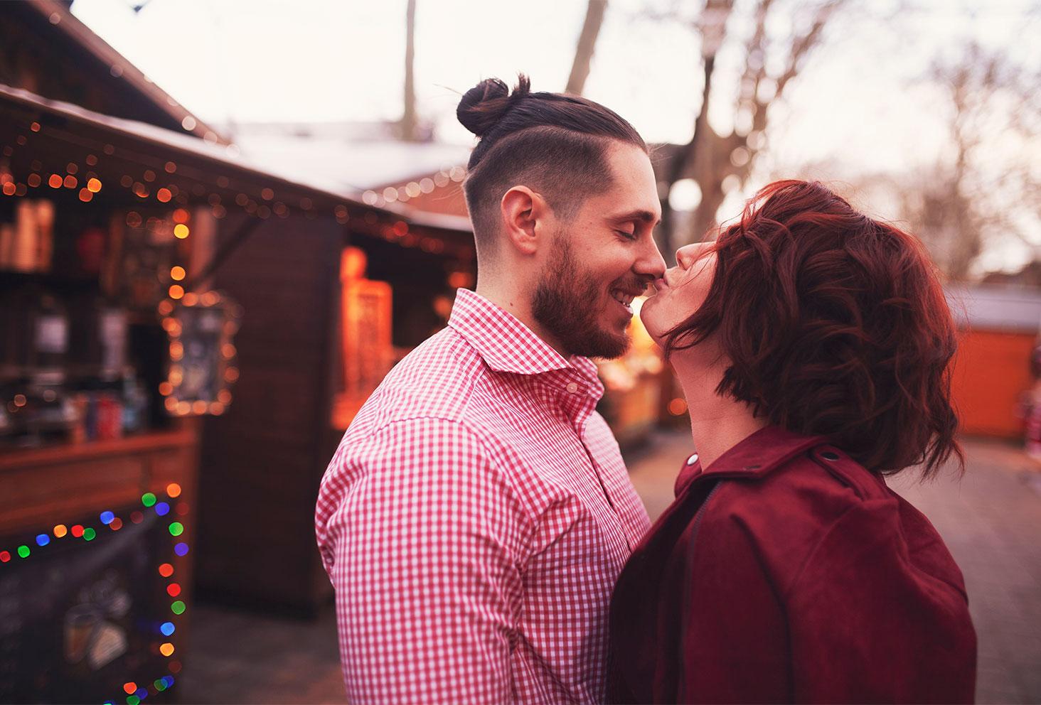 Bisou sur le nez de mon amoureux au milieu du marché de Noël en tenue de fêtes