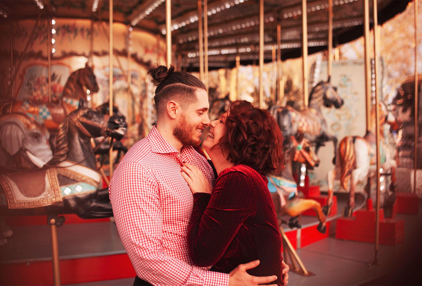 En amoureux dans les bras l'un de l'autre, devant le carrousel du marché de Noël en tenues de fêtes, pour fêter les 4 ans de blog