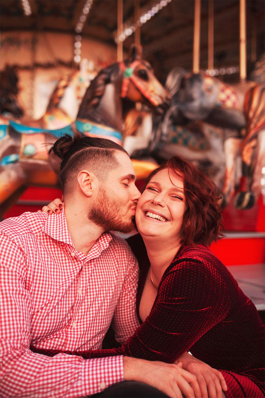 Bisou sur la joue de mon amoureux, assise sur le bord du carrousel du marché de Noël de Tours, en look de fêtes avec le sourire