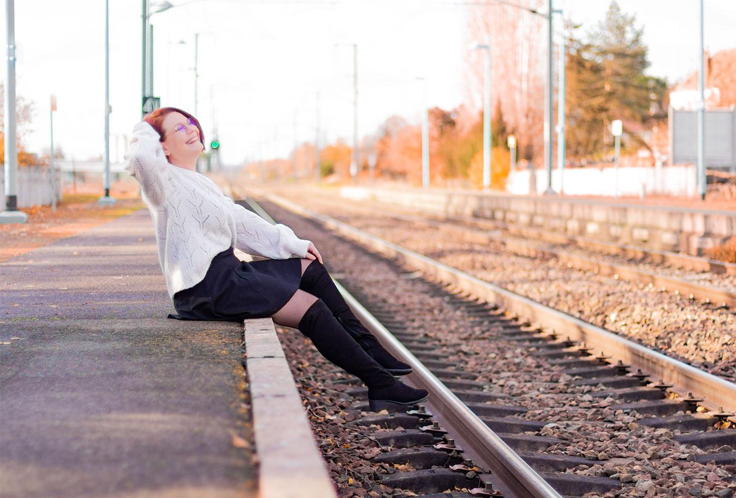 Assise sur le quai d'une gare en jupe patineuse noire Patatam et pull blanc, les jambes dans le vide, avec le sourire