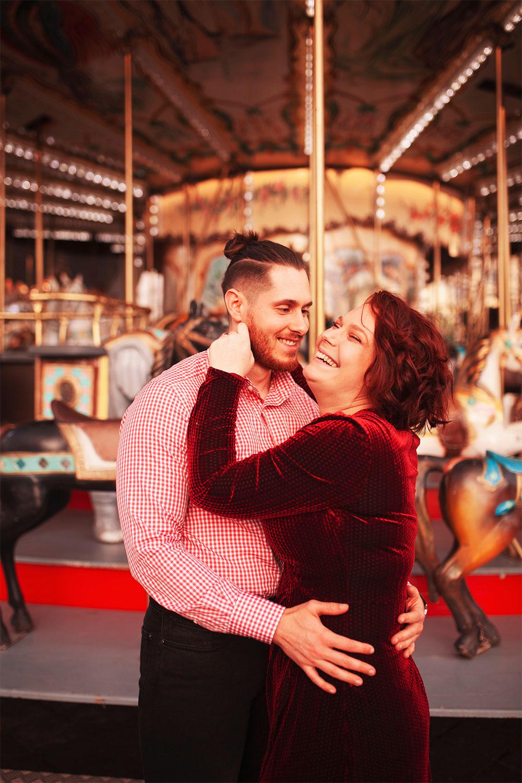Devant le manège du marché de Noël de Tours en amoureux, les bras dans les bras, en looks de fêtes