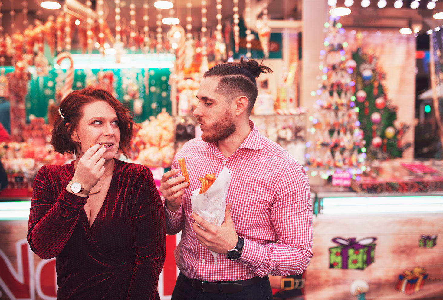 En amoureux en train de manger des chichis au marché de Noël en tenues de fêtes