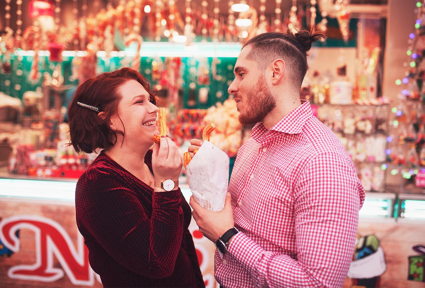 En train de manger des churros en amoureux devant le camion de chichis du marché de Noël, en tenues de fêtes avec le sourire