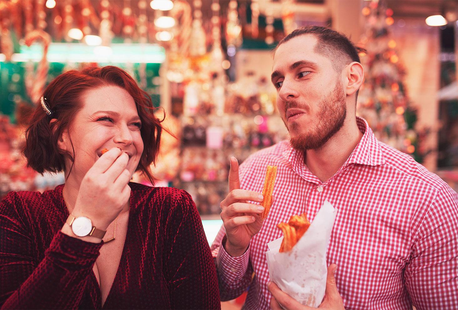 Fou rire en amoureux en train de manger des chichis sur le marché de Noël de Tours