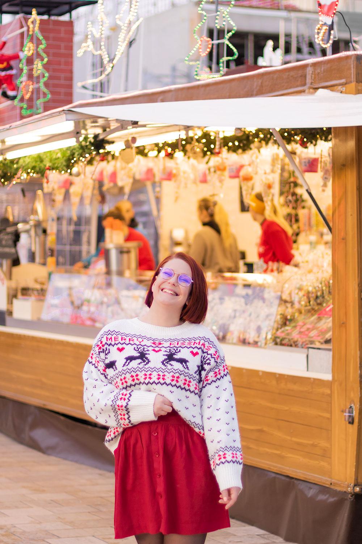 En pull de Noël et jupe fluide bordeaux trouvés sur Patatam, devant une cabane à chichis illuminés pour les fêtes