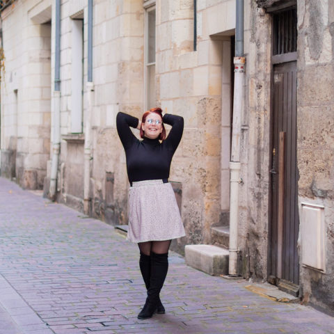 Au milieu d'une rue avec le sourire, habillée en total look, beige et noir, seconde main trouvé sur l'e-shop Patatam