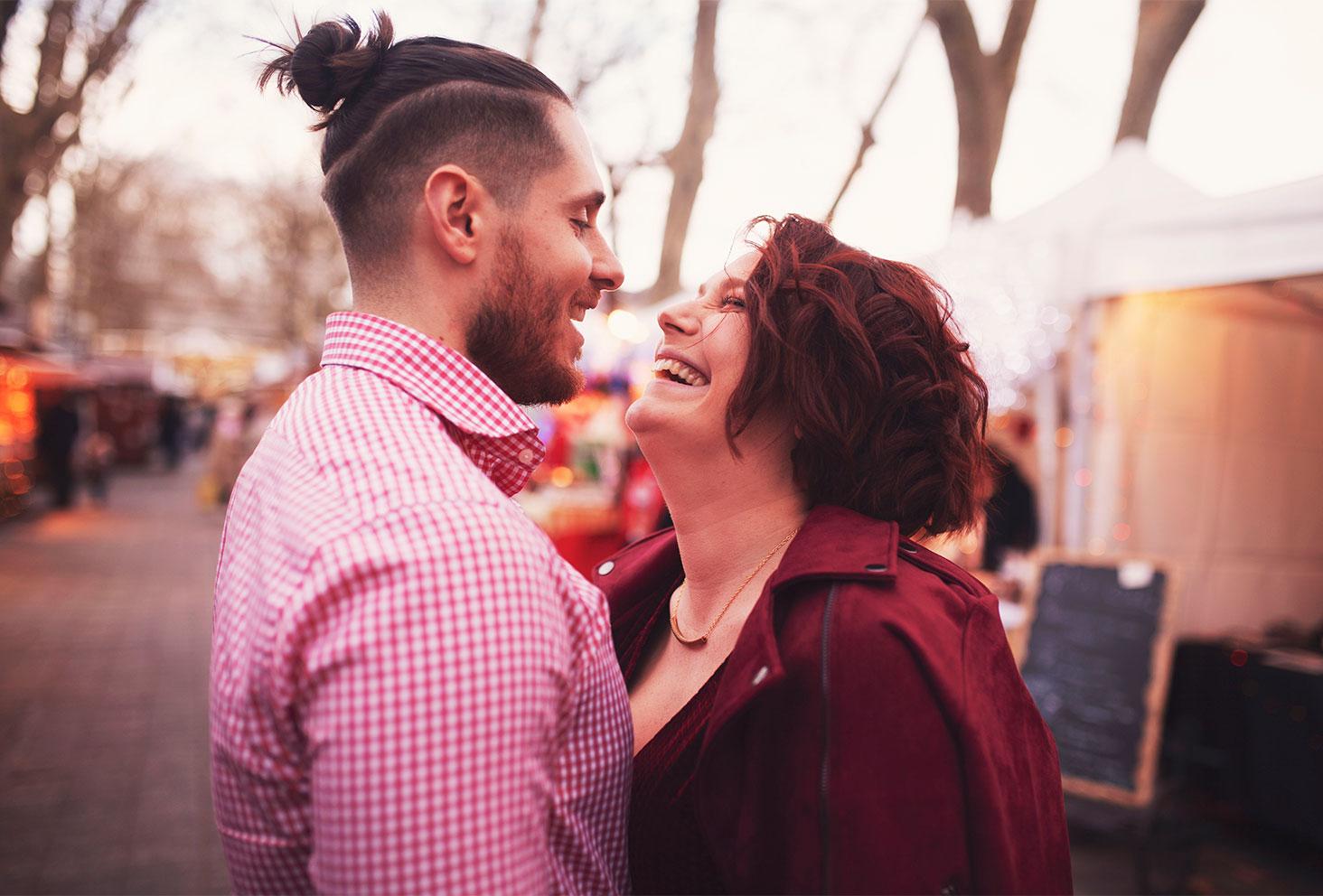 En amoureux sur le marché de Noël, les yeux dans les yeux avec le sourire