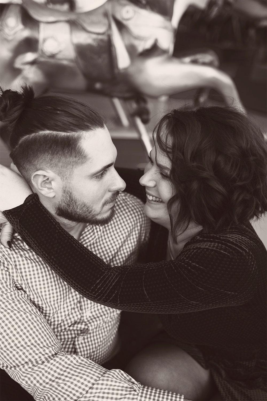 Assis en amoureux sur le bord d'un carrousel, avec le sourire, en noir et blanc
