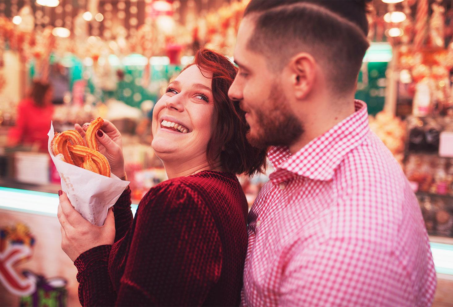 Shooting devant le camion de friandises sur le marché de Noël en amoureux, avec le sourire en tenues de fête, un cornet de chichis à la main