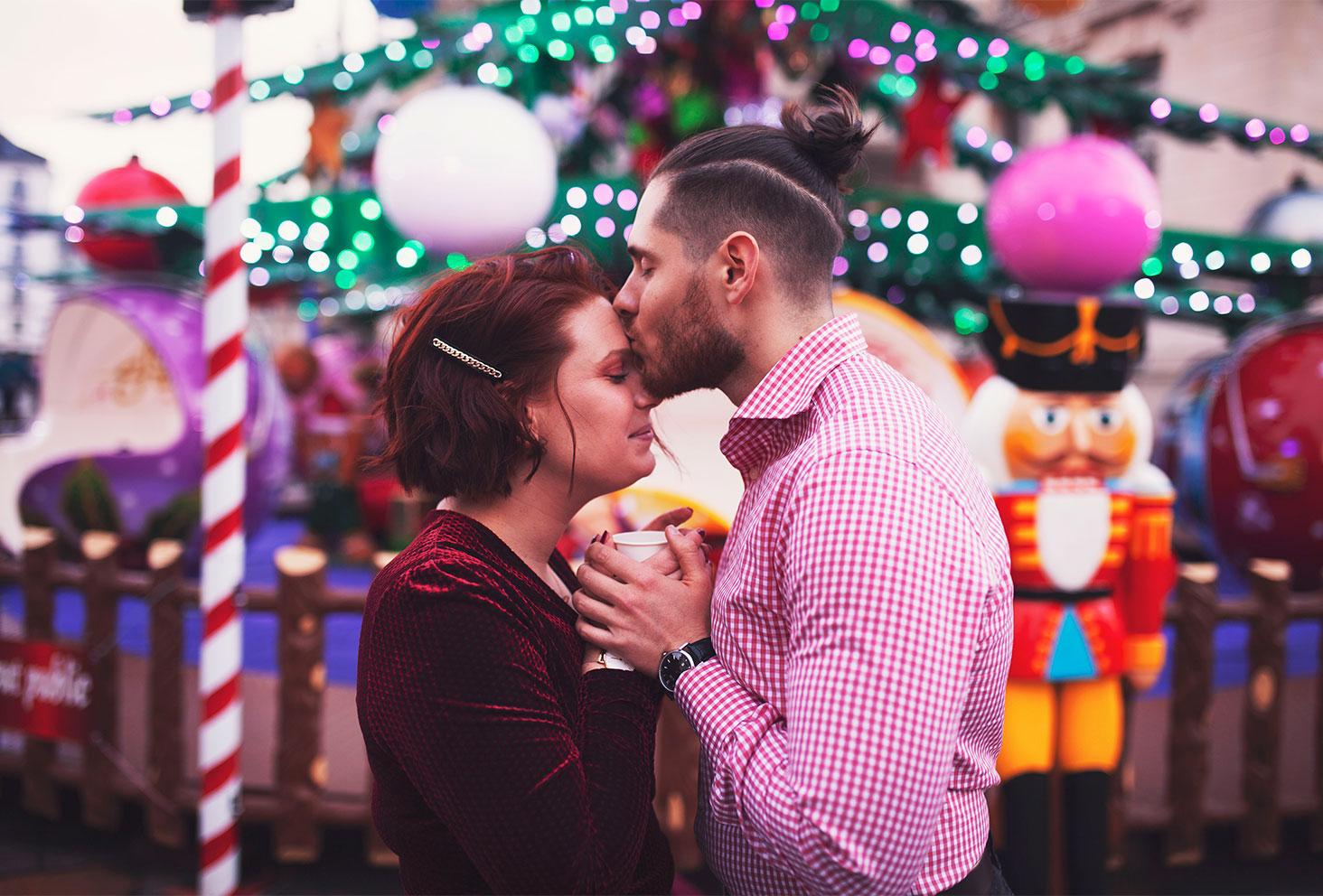 Devant un manège lumineux du marché de Noël de Tours, en amoureux un verre de cidre chaud entre les mains, un bisou sur le front avec le sourire