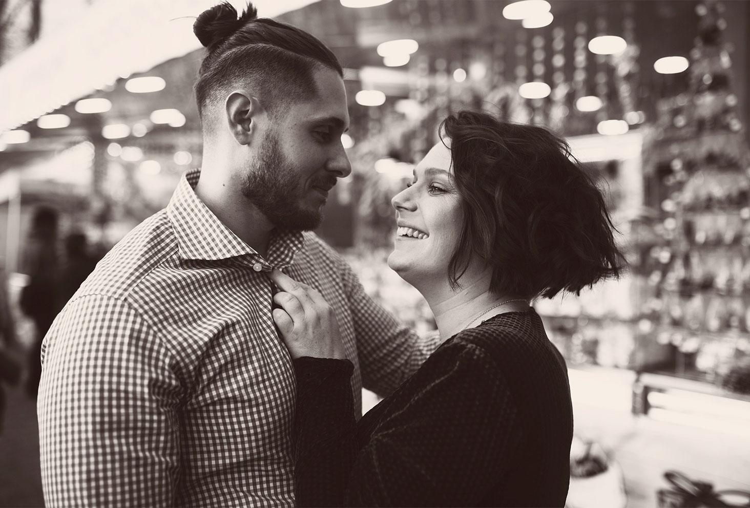 En amoureux devant les illuminations de Noël, avec le sourire, en tenues de fêtes en noir et blanc