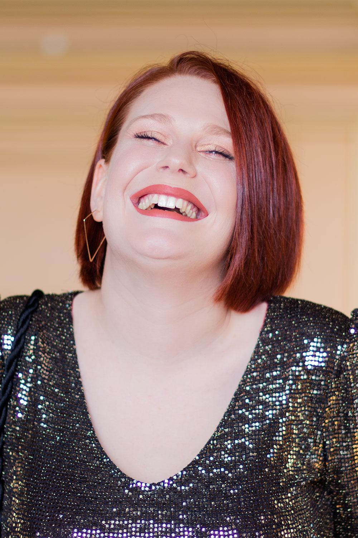 Portrait avec le sourire, du rouge à lèvres nude sur les lèvres et un body décolleté à paillettes
