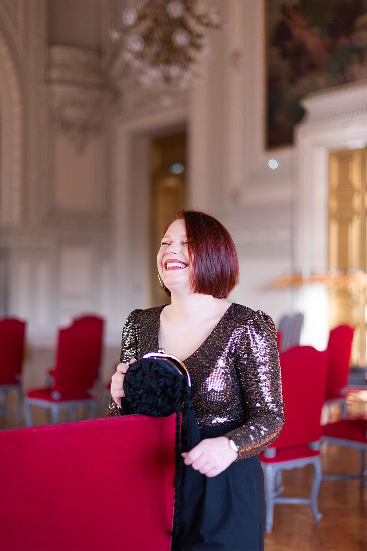 Appuyée le long d'une banquette rouge de l'hôtel de ville de Tours en tenue de fêtes pour la nouvelle année 2020