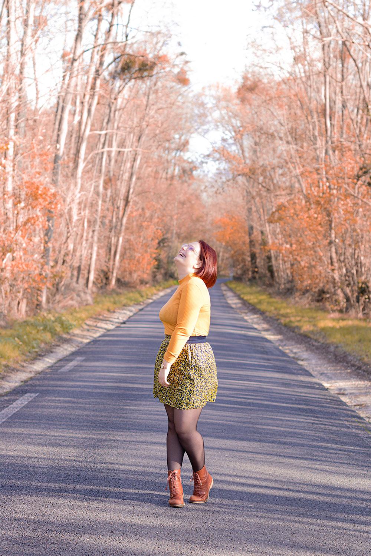 Au milieu d'une route perdu au milieu d'une forêt automnale, en sous-pull jaune et jupe bleue et jaune avec le sourire