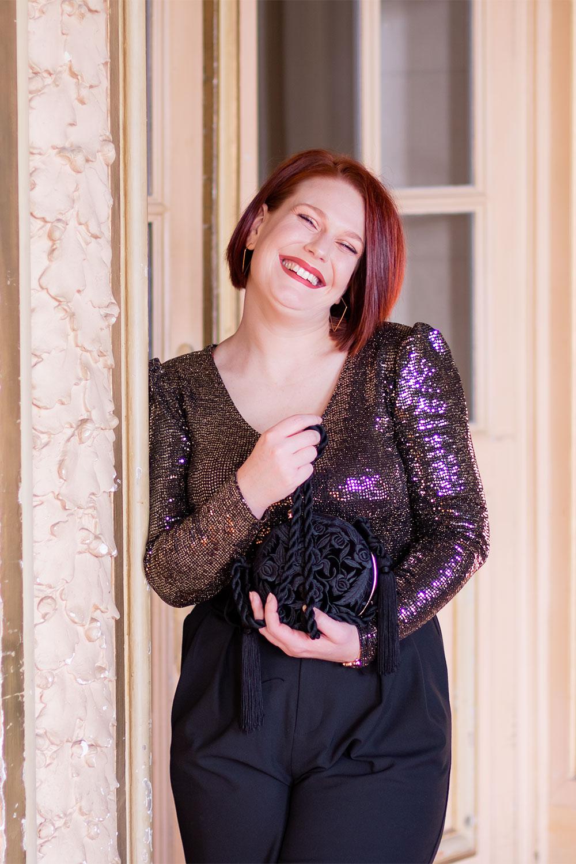 Appuyée le long d'une grande porte, en pantalon noir et body à paillettes, pour la nouvelle année avec le sourire