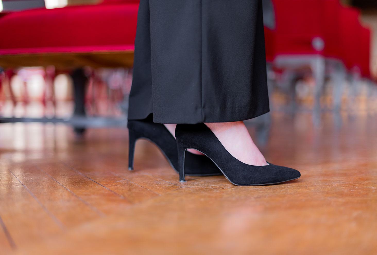 Zoom sur les escarpins en velours noirs porté avec un pantalon pattes d'éléphant noir