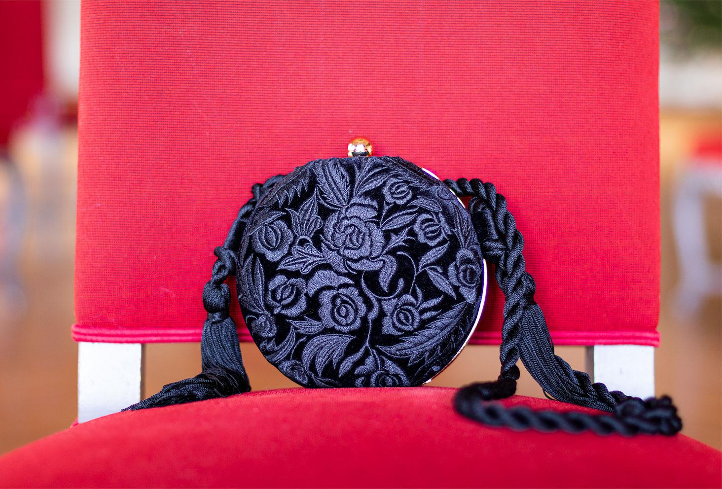 Zoom sur la pochette ronde et noire en velours posée dur un siège en tissu rouge de l'hôtel de ville de tours