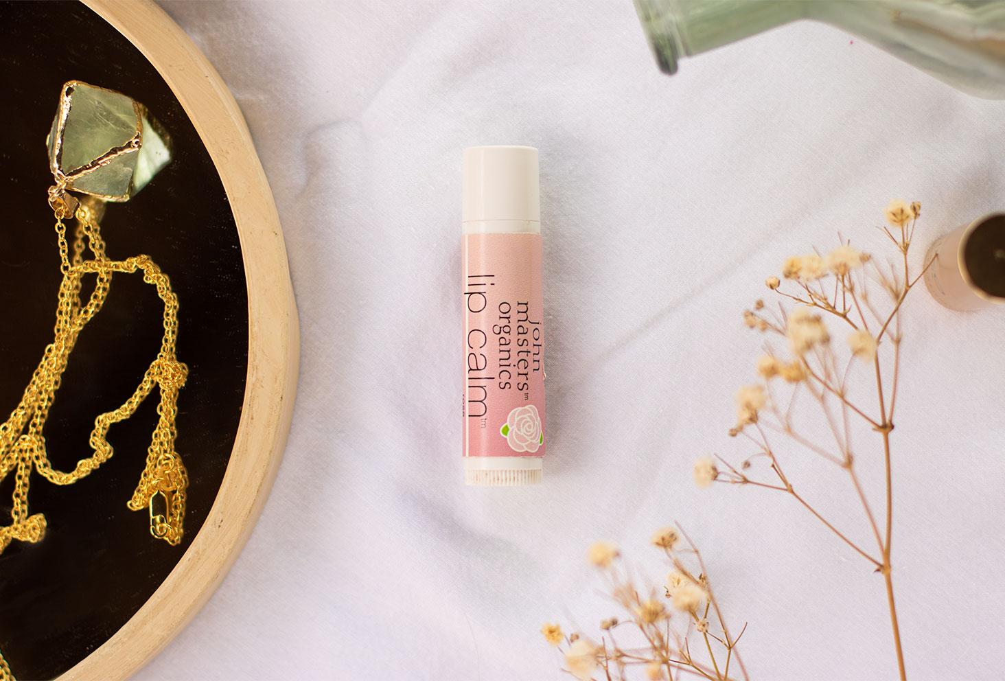 Zoom sur le baume à lèvres de John Masters Organics sur un drap blanc à côté de fleurs séchées
