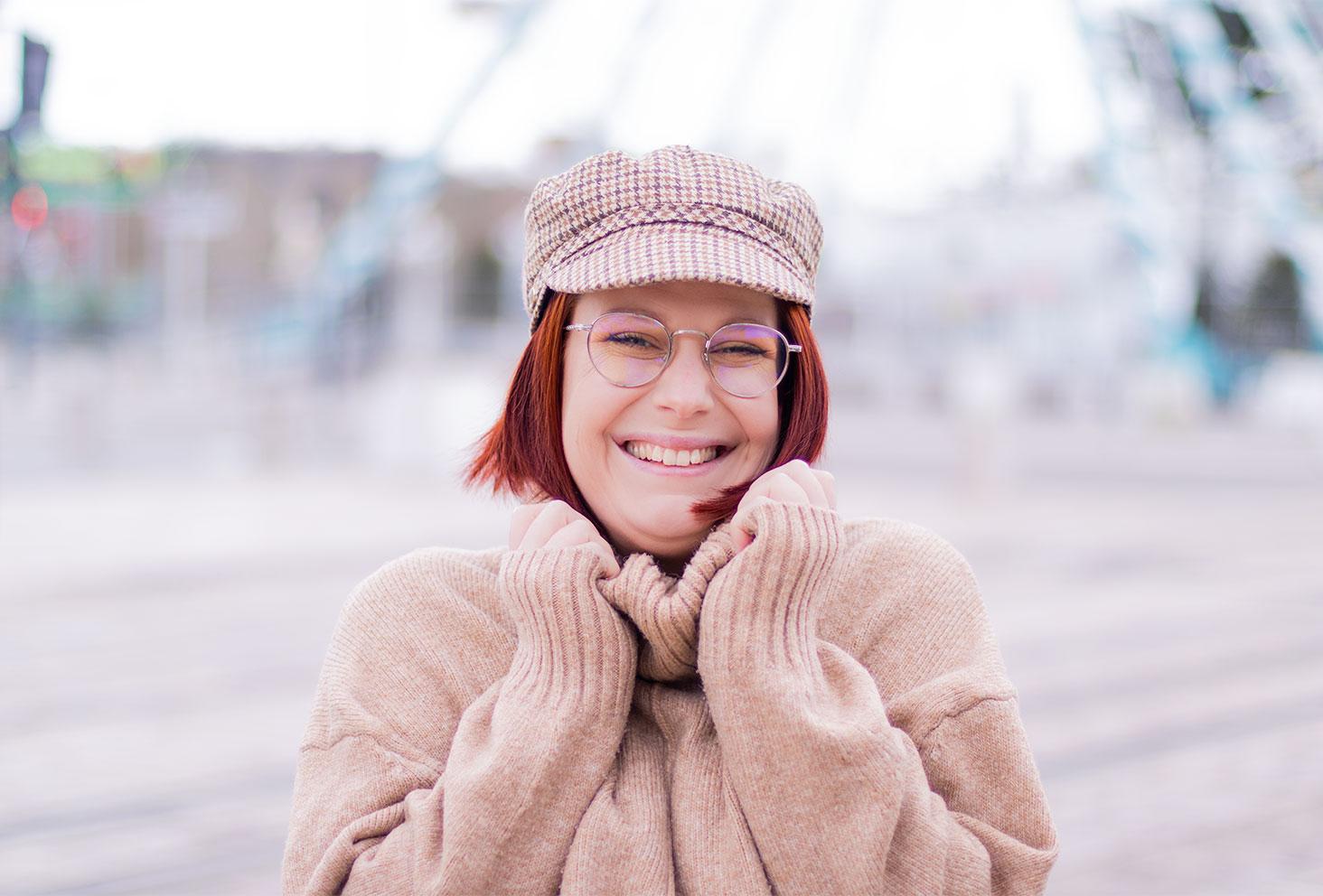 Une casquette de style marin à carreaux beiges et marrons portée, avec le sourire et un pull beige à col roulé
