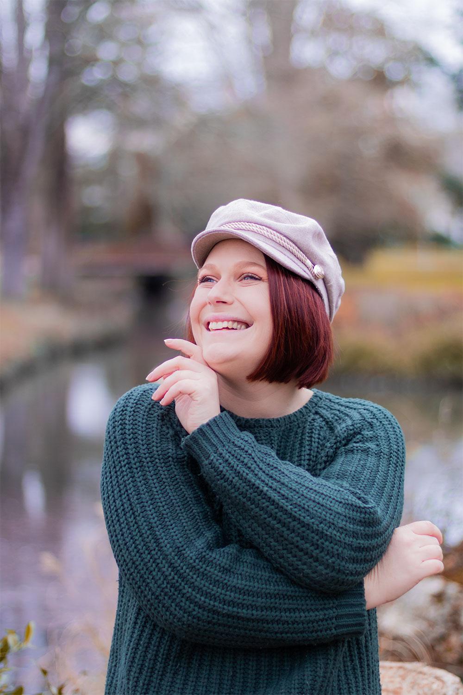 La casquette de style marin beige portée avec un pull en grosses mailles vert sapin, avec le sourire au milieu d'un parc