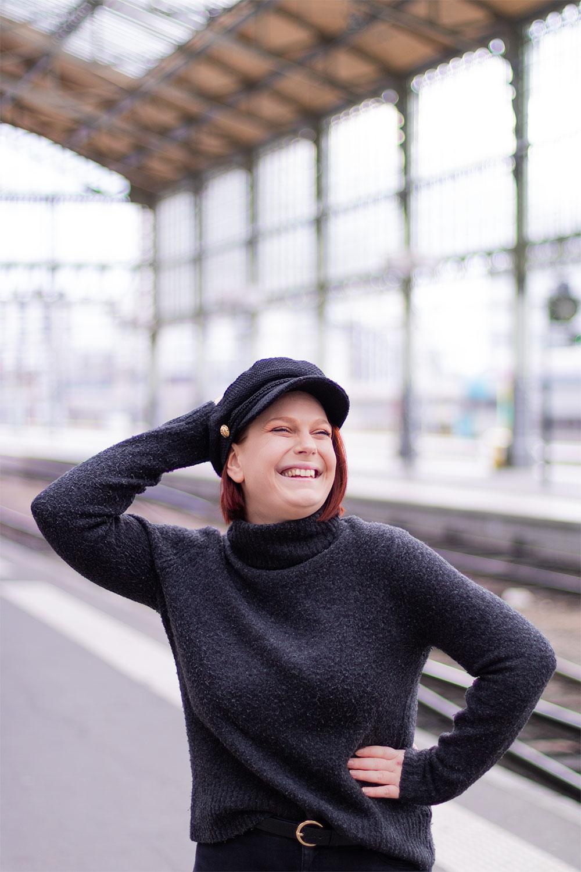 La casquette de style marin noire portée avec le sourire et un gros pull à col roulé gris, sur les quais d'une gare