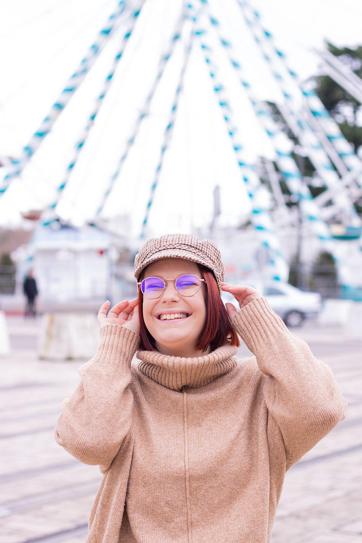 Avec le sourire et un gros pull beige devant la grand roue de Tours, une casquette à carreaux de style marin sur la tête