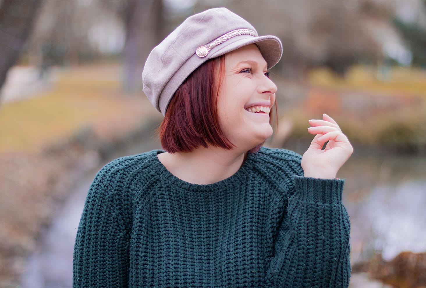 Zoom sur une casquette de style marin en feutre beige portée, au milieu d'un parc, avec le sourire