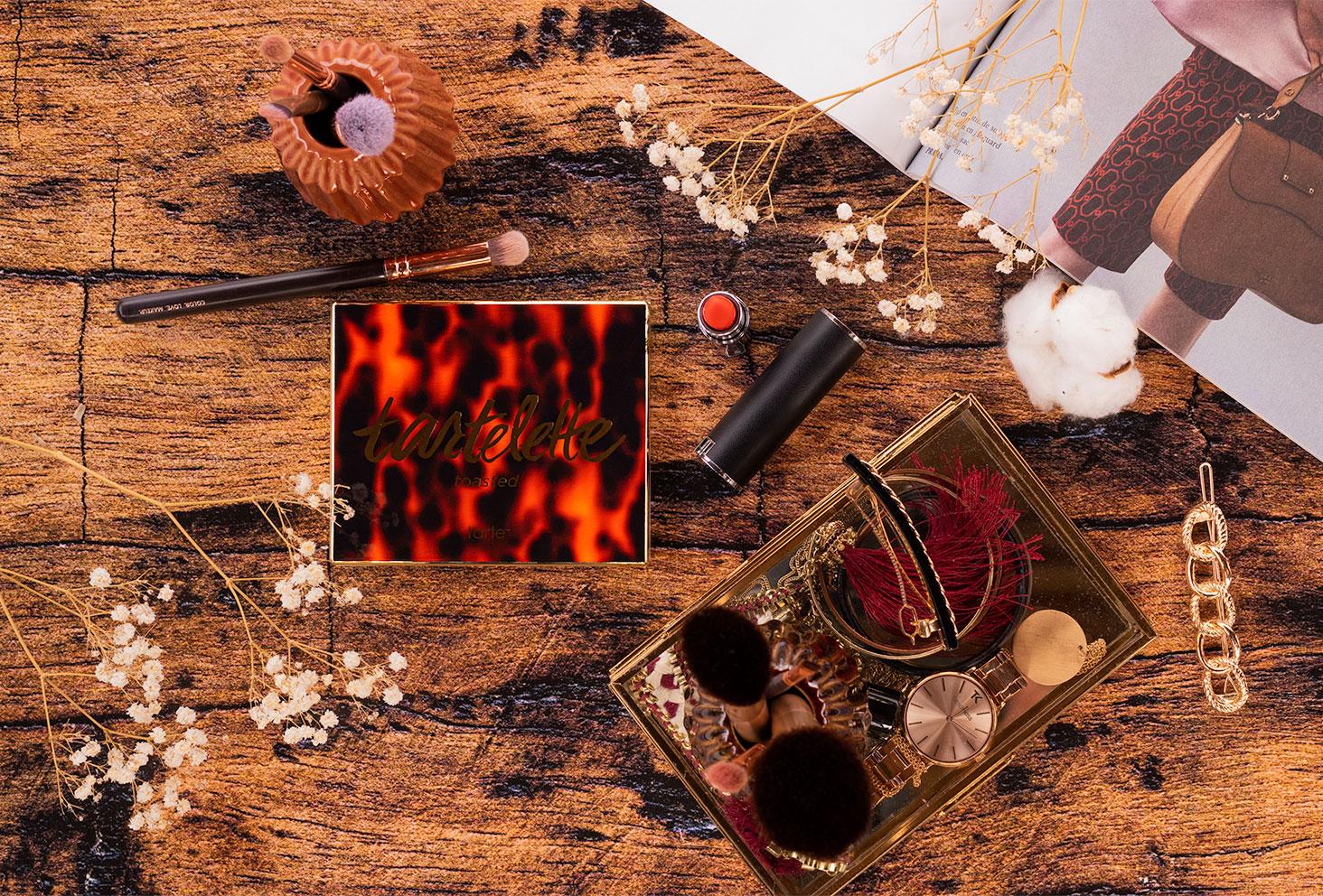 Flatlay de la palette Tartelette Toasted de tarte fermée sur un fond en bois au milieu de bijoux et de maquillage