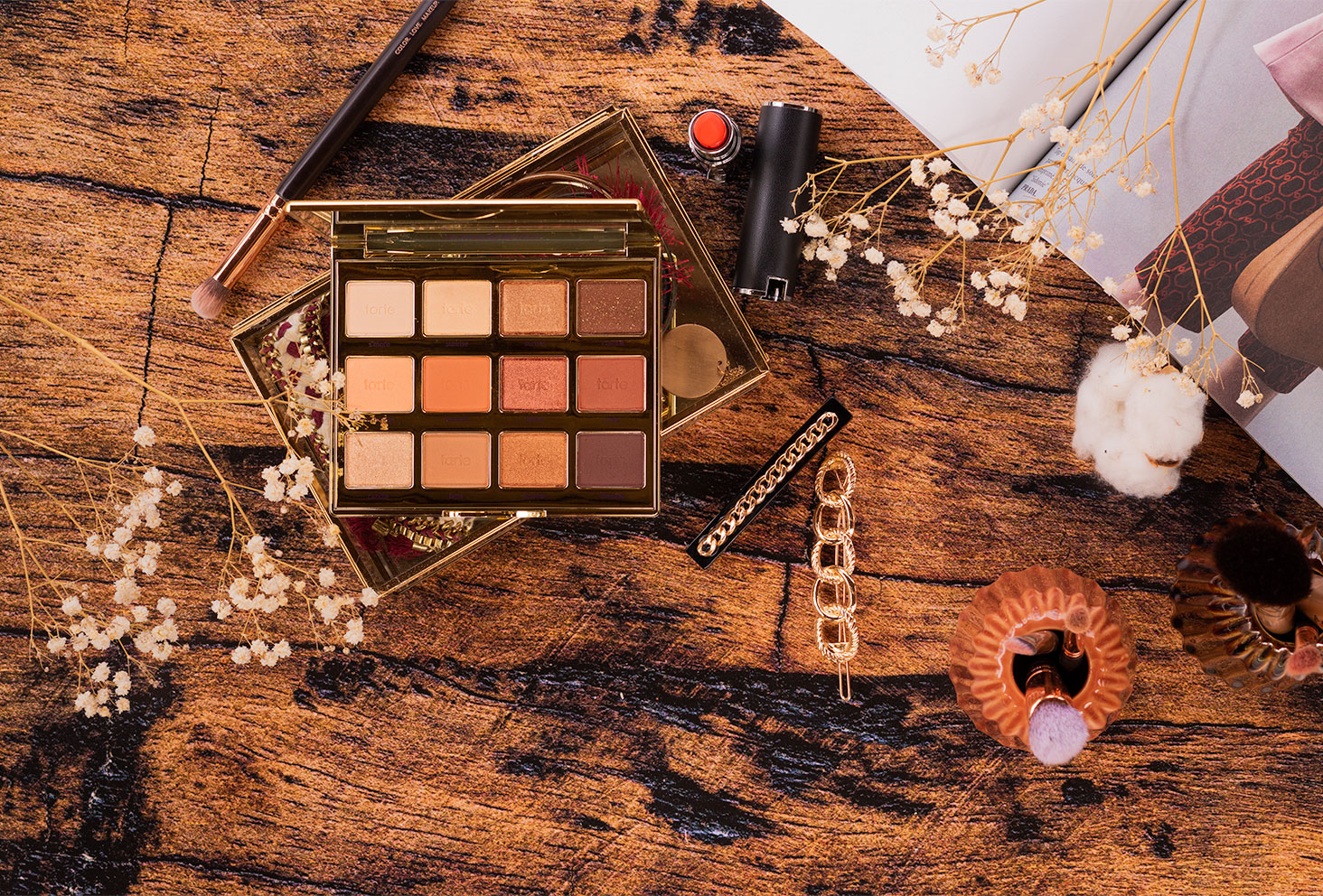 Flatlay de la palette Tartelette Toasted sur un fond en bois au milieu de bijoux et de make-up