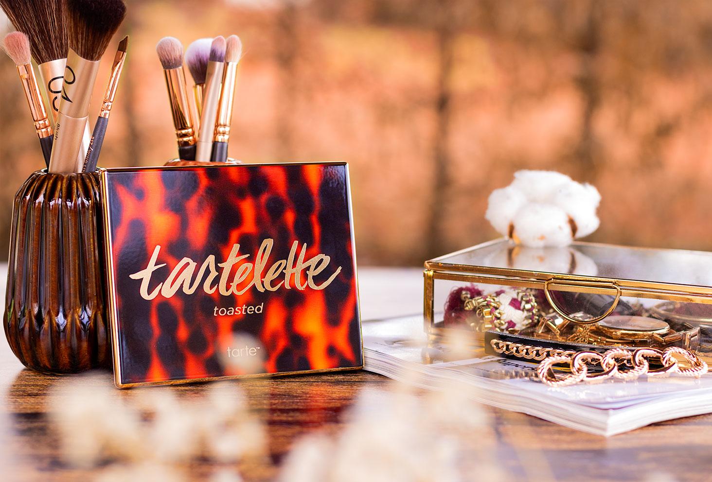 La palette Tartelette Toasted de Tarte appuyée le long de pots à pinceaux de maquillage, sur une table en bois, à côté d'une boîte à bijoux dorée
