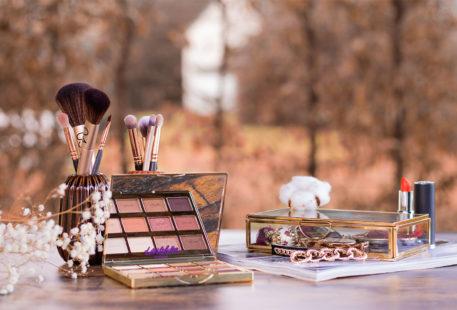 La palette Tartelette Toasted de Tarte posé sur une table en bois au milieu d'accessoires à maquillage