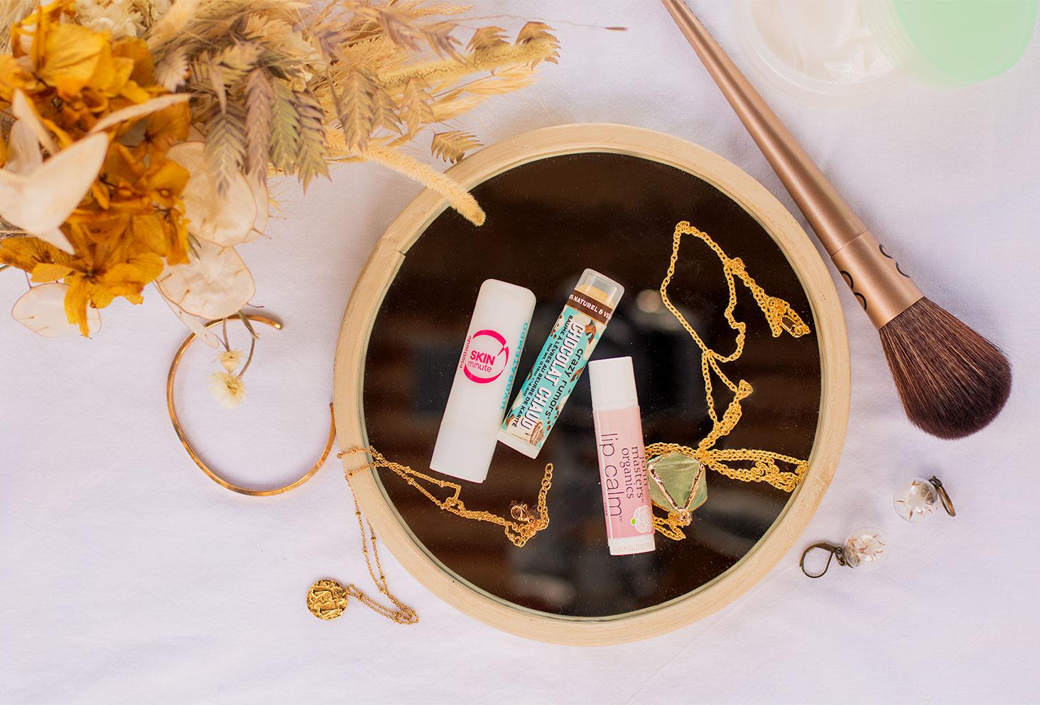 Photo flatlay des 3 meilleurs baumes à lèvres posés sur un miroir au milieu de bijoux et de fleurs séchées
