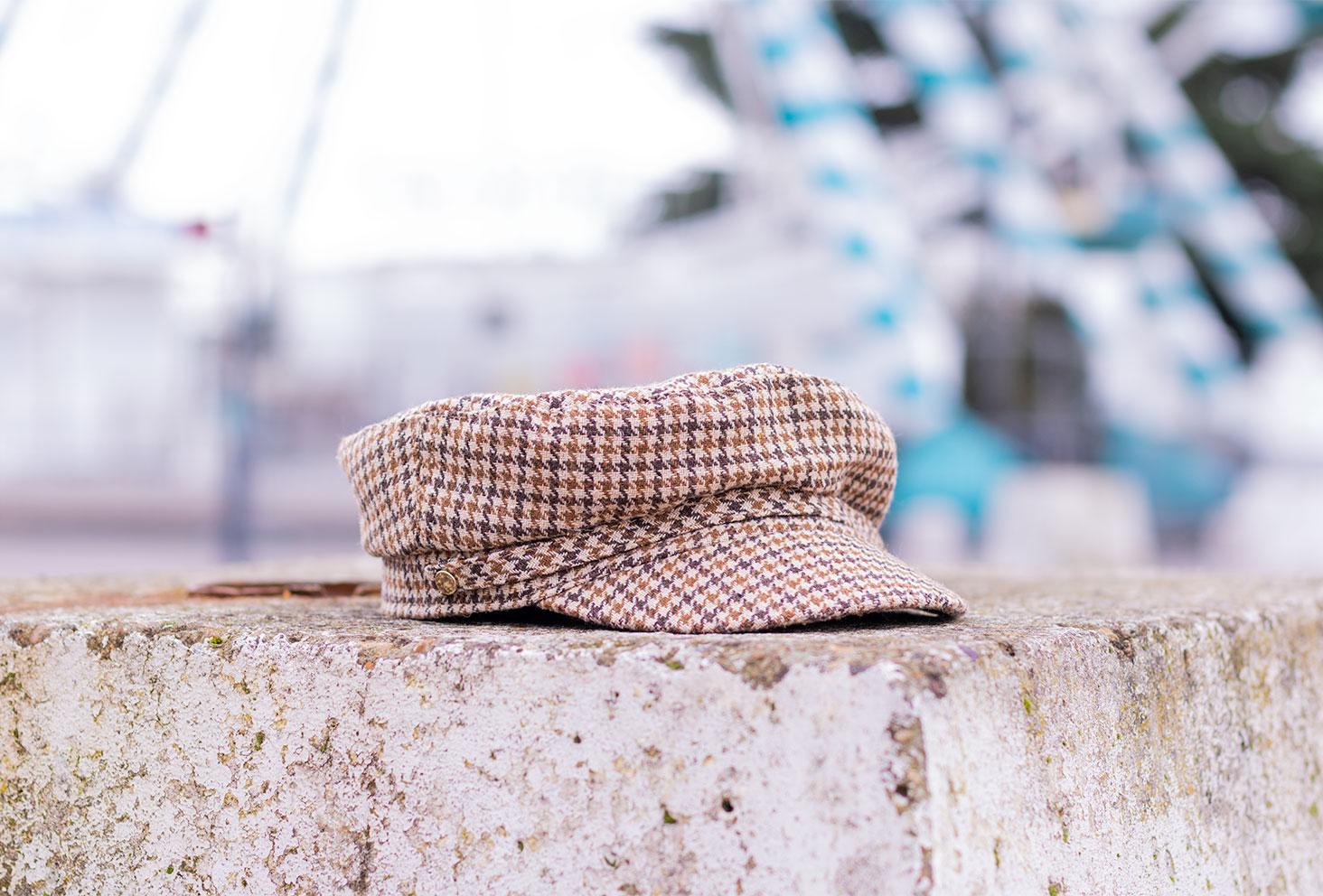 Zoom sur une casquette de style marin à carreaux beige et marron, non portée, posée sur un socle de béton devant une grand roue