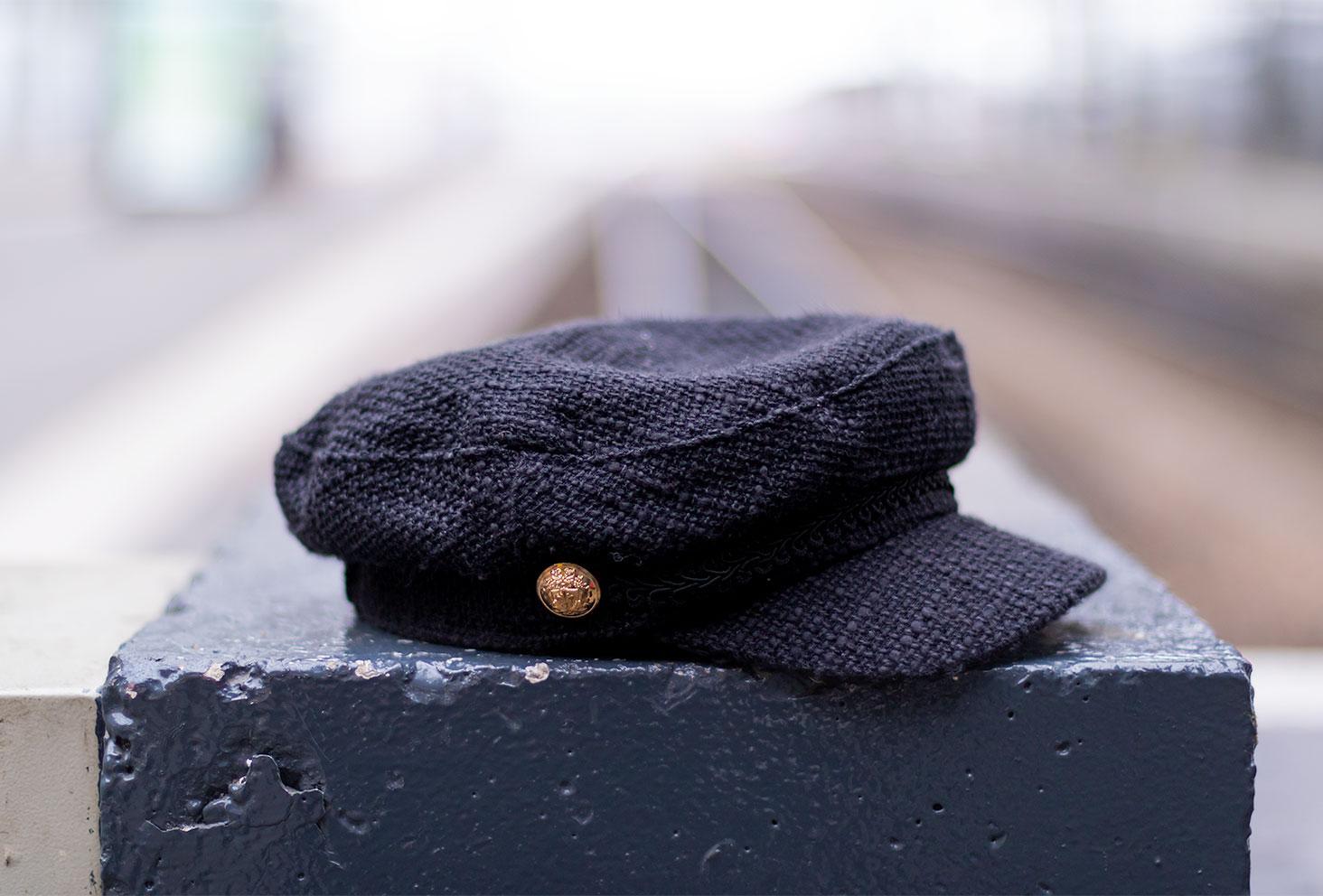 Zoom sur une casquette de style marin non portée noire, posée sur un socle de béton dans la gare de Tours