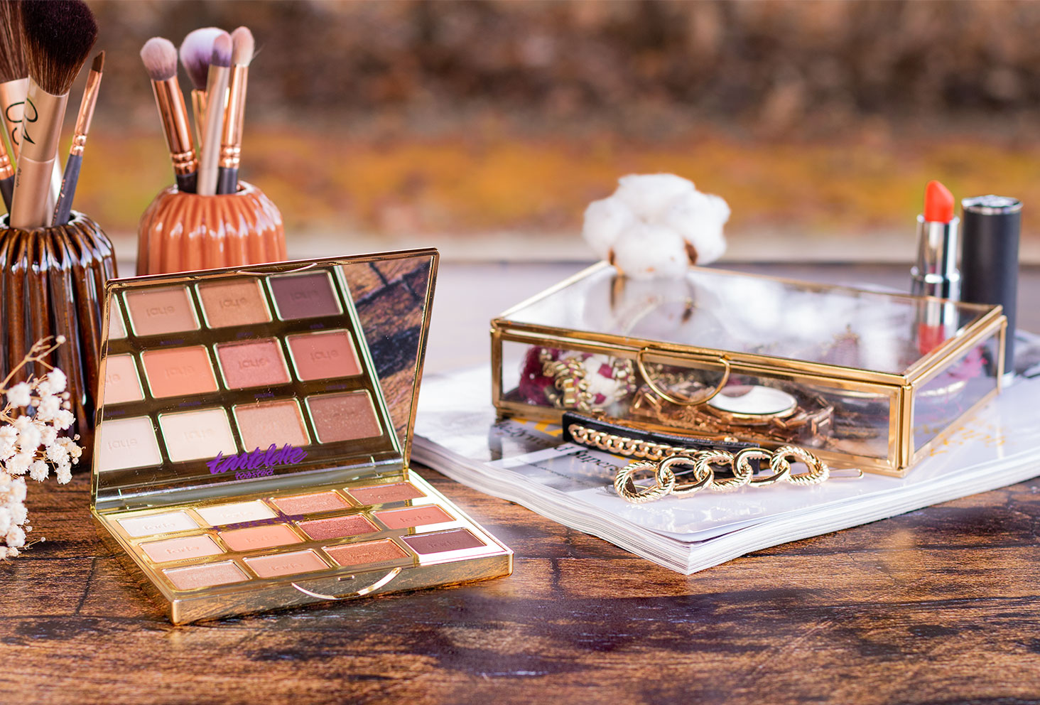 La palette Tartelette Toasted de Tarte ouverte au milieu d'accessoires à maquillage