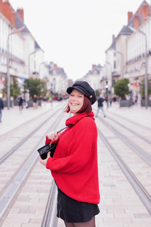 Dans la rue de profil avec le sourire et une casquette sur la tête, en pull rouge, pour parler du harcèlement de rue