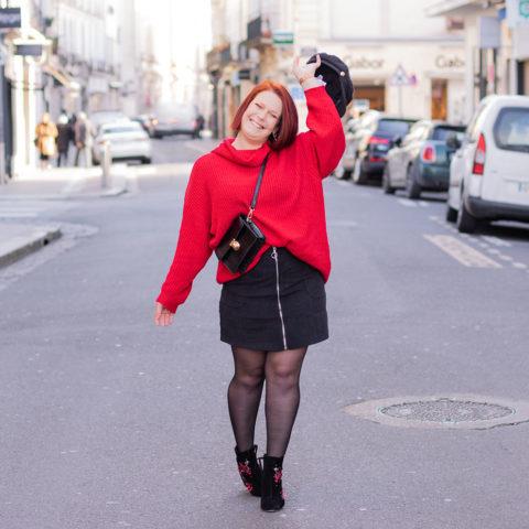 Dans la rue avec le sourire, en pull rouge et jupe en velours Shein, la casquette dans la main au dessus de la tête