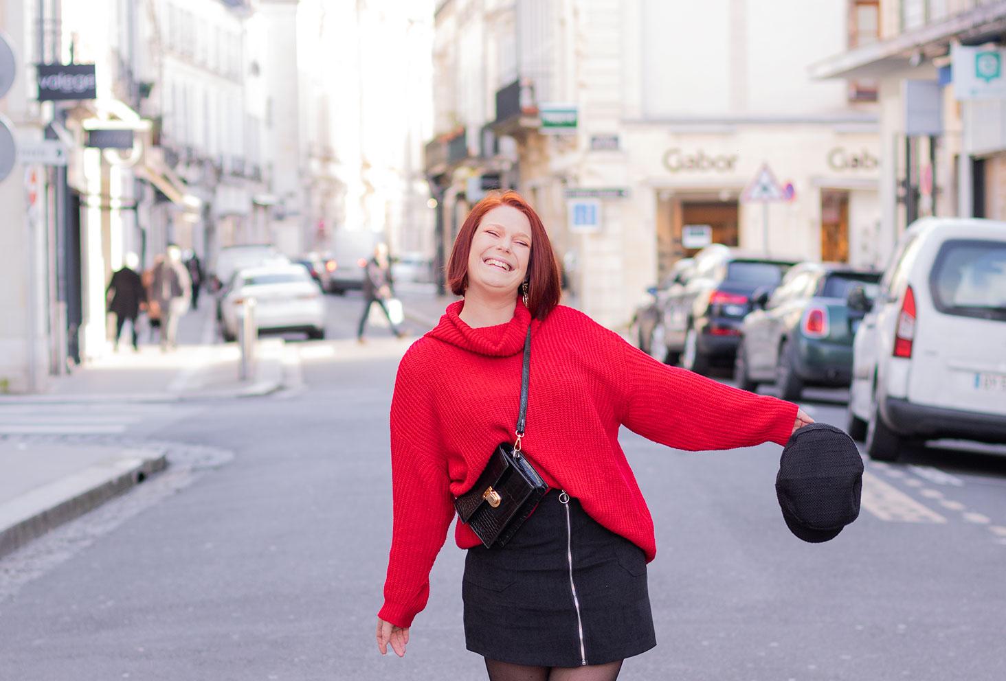 Dans la rue en pull rouge Shein, jupe noire en velours, avec une casquette dans la main et le sourire