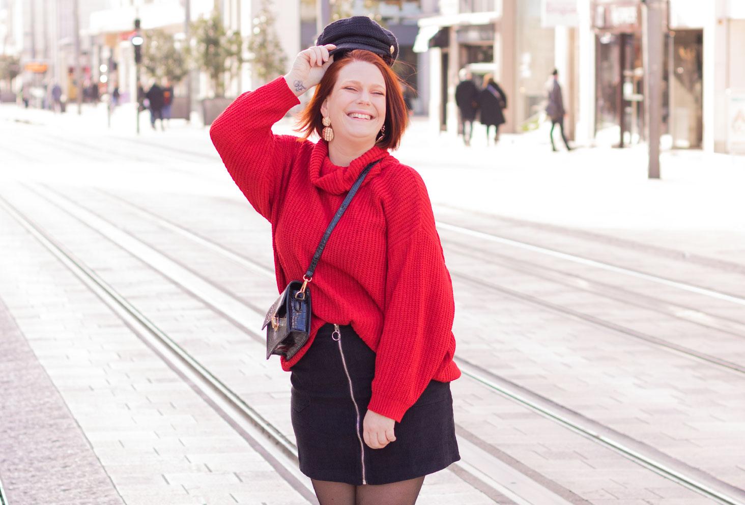 Au milieu d'une rue en jupe noire et pull rouge Shein, pour parler du harcèlement de rue