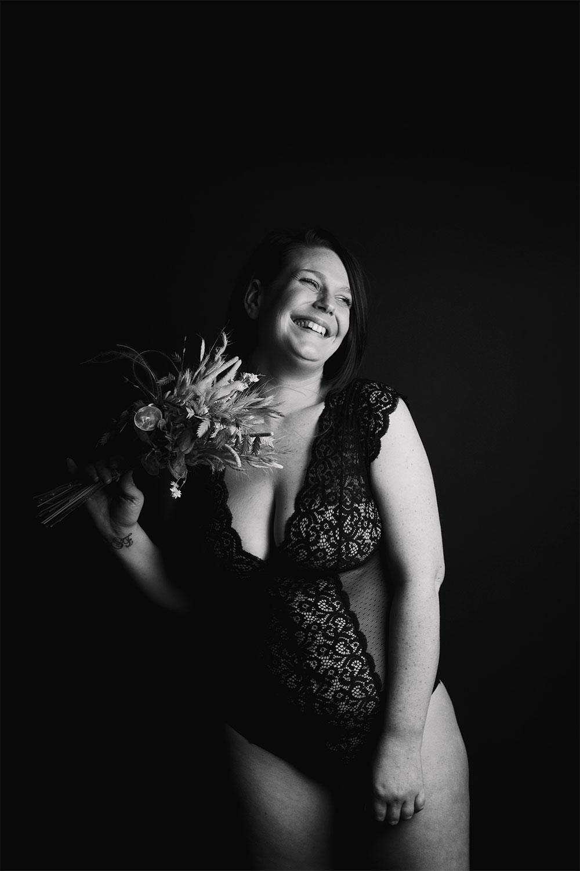Body en dentelle noir Pomm'Poire avec un bouquet de fleurs séchées à la main, en studio, pour la mise en avant du body positive