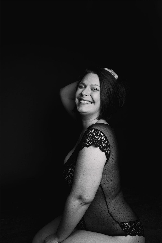 Shooting studio à Tours en noir et blanc, avec le sourire en body noir en dentelle