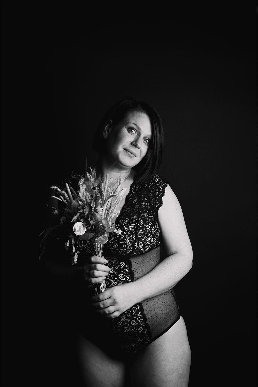 Shooting en body noir Pomm'Poire, un bouquet de fleurs dans les mains, pour le body positive