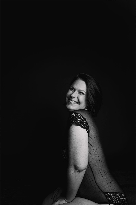 Shooting studio en noir et banc, assise avec le sourire en body en dentelle noir
