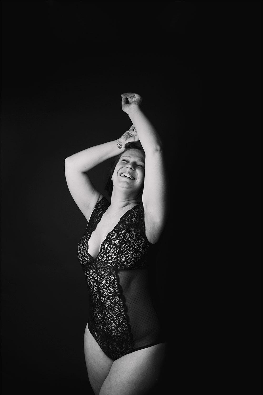 Avec le sourire pour parler de body positive, shooting photo en studio avec le sourire, en body noir à dentelles