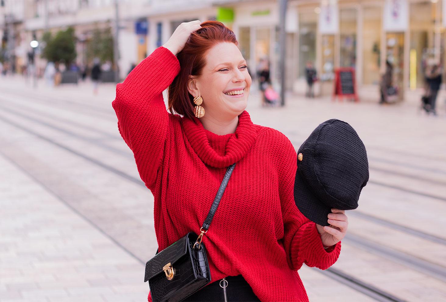 Zoom sur le sourire avec un pull rouge et une casquette noire dans la main, au milieu de la rue