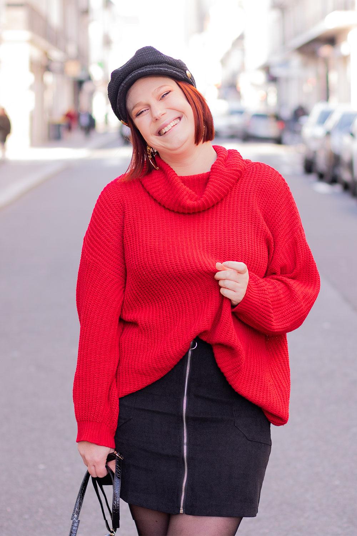 Zoom sur le pull oversize rouge Shein, porté avec une jupe en velours noire et une casquette sur la tête