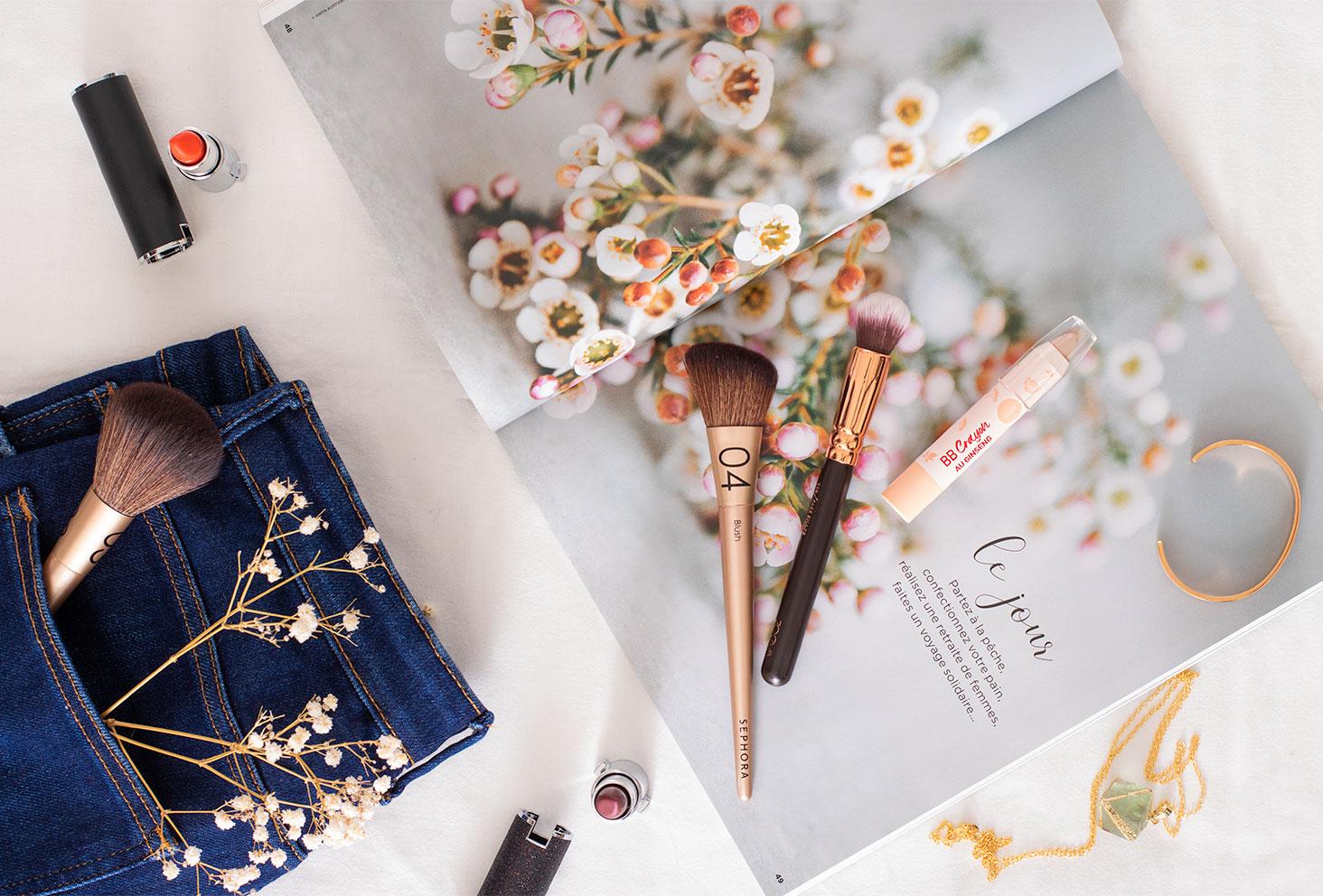 Le BB crayon Erborian posé sur un magazine ouvert à côté d'un jean plié et de pinceaux