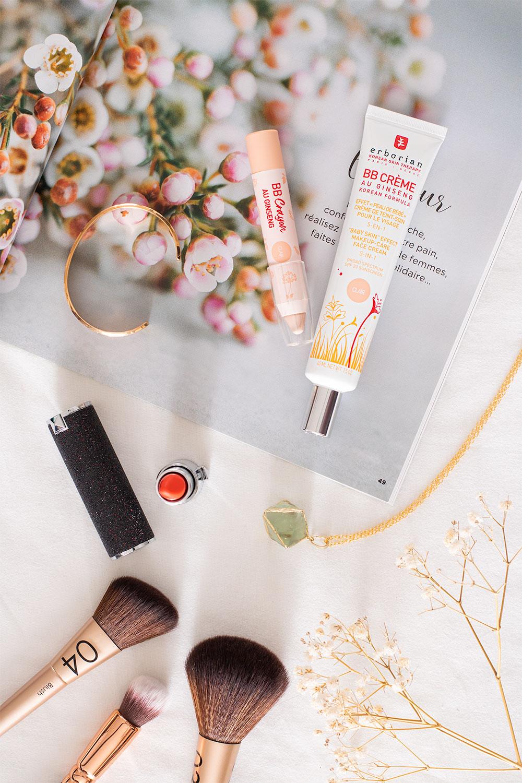 La BB crème et le BB crayon Erborian posés sur un magazine ouvert au milieu de pinceaux, de bijoux et de rouges à lèvres, sur une couette blanche