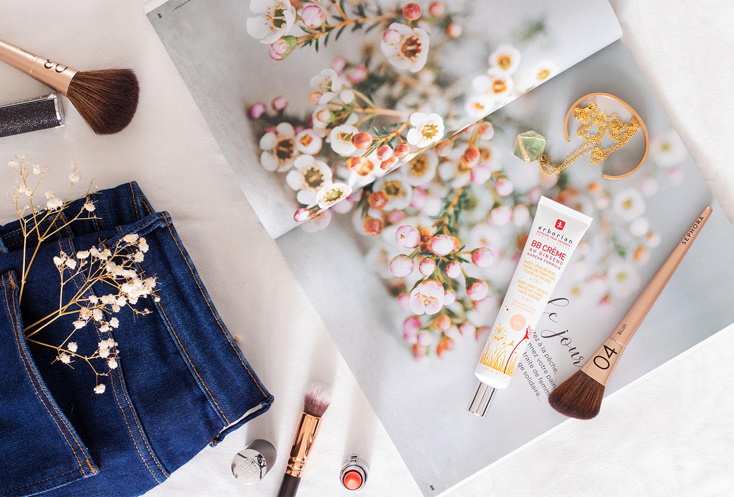 La BB crème Erborian posé sur un magazine fleuri ouvert sur un drap blanc, au milieu de pinceaux et de rouges à lèvres