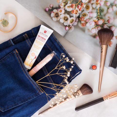 La BB crème et le BB crayon Erborian dans une poche de jean plié, à côté d'un magazine, au milieu de bijoux et d'éléments de maquillage, sur un drap blanc